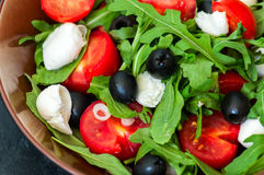 Close up of fresh salad with rucola, tomatoes cherry, olives, sp Royalty Free Stock Photos