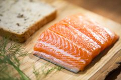 Close up of a fresh salmon steak fillet lying on a wooden plate with a dill, bread and lemon. Set with a fish, herb and whole wheat bread on a cutting board Royalty Free Stock Photo