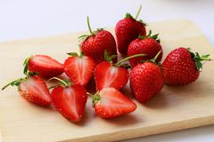Close up fresh strawberries cut in half and whole strawberries on cutting board royalty free stock photos