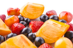 Close-up fresh strawberry, persimmon, black and red cherry with white background. Stock Photo