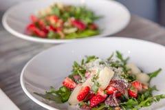 Close-up fresh summer salad with basturma jerky, greens, arugula, strawberries, melon, parmesan cheese. Concept delicacy, new menu stock image