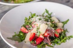 Close-up fresh summer salad with basturma jerky, greens, arugula, strawberries, melon, parmesan cheese. Concept delicacy, new menu. Closeup fresh summer salad stock images
