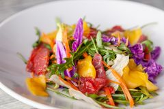 Close-up fresh summer salad with bresaola meat, greens, arugula, mango, carrot, Chinese cabbage. Concept Italian delicacy, new royalty free stock photos