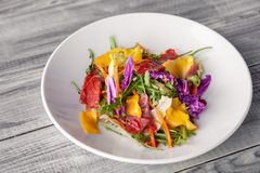 Close-up fresh summer salad with bresaola meat, greens, arugula, mango, carrot, Chinese cabbage. Concept Italian delicacy, new royalty free stock image
