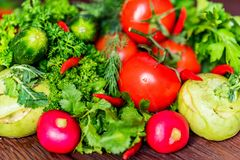 Fresh vegetables and herbs on wooden table. Close up fresh tomatoes, radish, dill, parsley, kohlrabi and ramsons on dark wooden surface Stock Photography
