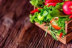 Fresh vegetables and herbs in wooden box. Close up fresh tomatoes, radish, dill, parsley, kohlrabi and ramsons in wooden box on dark wooden surface Stock Photos