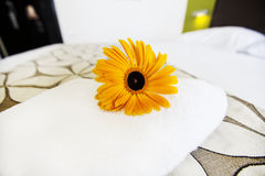 Close up a fresh towel with yellow flower on the bed Royalty Free Stock Photography