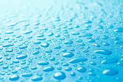 Close-up of fresh water drops on blue surface Royalty Free Stock Photography