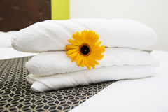A fresh white towel with yellow flower on the bed Stock Image