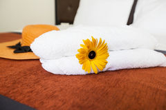 Close up a fresh white towel with yellow flower and hat on the bed room. Stock Photos