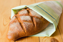 Close up of fresh whole wheat bread in green white napkin on wooden table Stock Photos