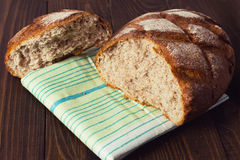 Close up of fresh whole wheat bread laying in green white napkin on dark wooden table Royalty Free Stock Photos
