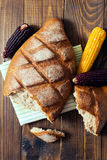 Close up of fresh whole wheat bread laying in green white napkin on wooden table with black and yellow corn Royalty Free Stock Images