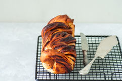 Close up of freshly baked delicious chocolate braided bread on a. Wire rack on a white stone background Stock Image