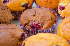 Close-up of freshly baked muffins in paper cups. Close-up of freshly baked chocolate and lemon cherry muffins in their decorative paper cups Stock Photos