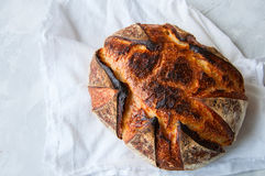Close up of freshly baked sourdough bread on a white stone backg. Round. Top view and copy space Stock Image