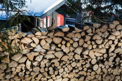 Close up of freshly chopped wood pile with a cabin in the backgr Royalty Free Stock Images