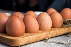Close up. Freshly harvested eggs in a wooden tray. Rustic organic products royalty free stock photo