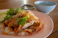 Close up Fried-Chicken Rice in a plate and sprinkle with coriander. With chicken broth And a cup of dipping sauce on a wooden stock photo