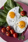 Close up fried eggs breakfast with salad and tomatoes at plate royalty free stock photos