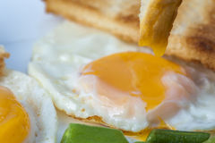 Close up of fried eggs, green beans with piece of toast on white plate. English breakfast. Royalty Free Stock Image