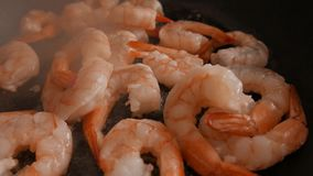 Close up of fried large prawns in a frying pan with oil. 4K UHD stock video footage