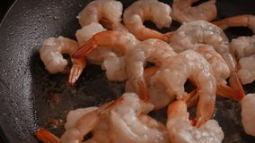 Close up of fried large prawns in a frying pan with oil. 4K UHD stock footage