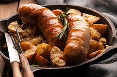 Close up of fried potatoes and grilled sausages in pan with fork, knife and grey napkin stock photography