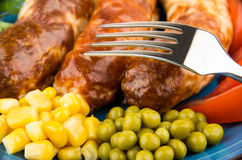 Close up of fried sausage with green peas, sweet corn Stock Images