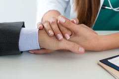 Close-up of friendly female medicine doctor's hand holding male. Patient's hand to support him. Bad news, stress and depression concept Royalty Free Stock Images