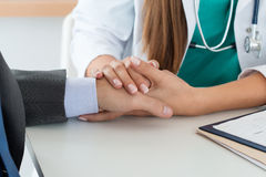 Close-up of friendly female medicine doctor's hand holding male Stock Photography