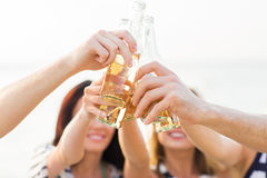 Close up of friends clinking bottles with drinks Royalty Free Stock Photography