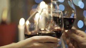 Close-up of friends clinking red wine and champagne glasses in the restaurant. Action. Friend`s meeting royalty free stock images