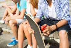 Close up of friends with longboard on street Stock Image