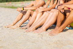 Close up of friends sitting on summer beach stock photos
