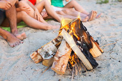 Close up of friends sitting on summer beach. Friendship, happiness, summer vacation, holidays and people concept - close up of friends sitting near fire on beach Royalty Free Stock Images
