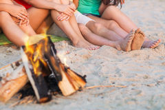 Close up of friends sitting on summer beach. Friendship, happiness, summer vacation, holidays and people concept - close up of friends sitting near fire on beach Stock Photography