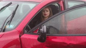 Close-up of a frightened girl sitting in the car after an accident in the rain. Close-up of a frightened girl sitting in the car after an accident in the rain stock footage