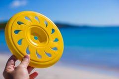 Close up frisbee background a tropical beach and. Close up frisbee against a tropical beach and sea Stock Photos