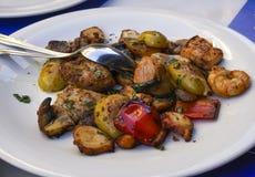Close up fritado do marisco da mistura, servido em um prato branco com colher Foto de Stock Royalty Free
