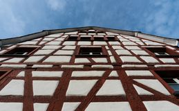 Close up frog perspective view of a half-timbered truss house with white walls and red wooden beams under a blue sky. In the picturesque village of Neunkirch in stock photos