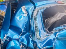 Close-up front of blue new car distorted by accident. Crashed ne Royalty Free Stock Photography