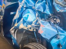 Close-up front of blue new car distorted by accident. Crashed ne Royalty Free Stock Photo