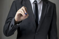 Close-up of front faced businessman is writing on the board. (focus on hand, blur out the suit). It can be used for layout in business-related words and objects Stock Photography