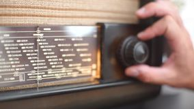 Close-up of the front glass and tuning handle of an old radio. Close-up of the front glass and tuning knob of the old radio, tuning the radio wave stock footage