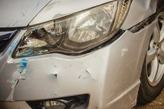 Close-up front of new silver car distorted by accident. Crashed Royalty Free Stock Images
