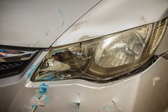 Close-up front of new silver car distorted by accident. Crashed Royalty Free Stock Photos
