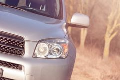 Close up front vew silver SUV car in the forest. Detail of a modern car. Head light royalty free stock image