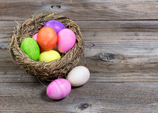 Close up front view of colorful Easter eggs in bird nest on rust. Ic wooden boards stock photos