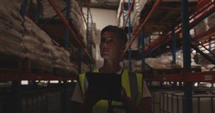 Female warehouse worker patrolling warehouse corridor at night 4k stock video footage